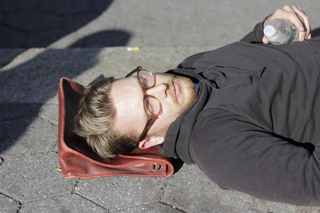 路上で寝る男